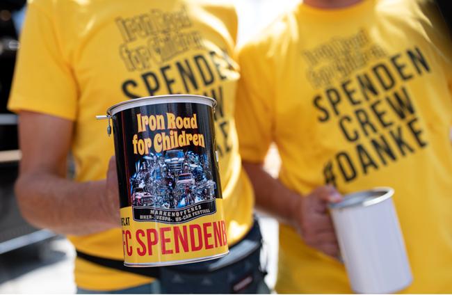 Zwei Mitarbeiter der Ironroad for Children Spendencrew die eine Spendendose in die Kamera halten